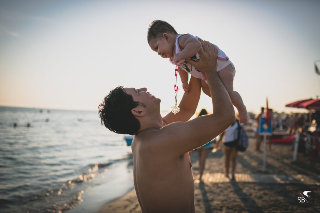 immagine di papà che alza la bimba