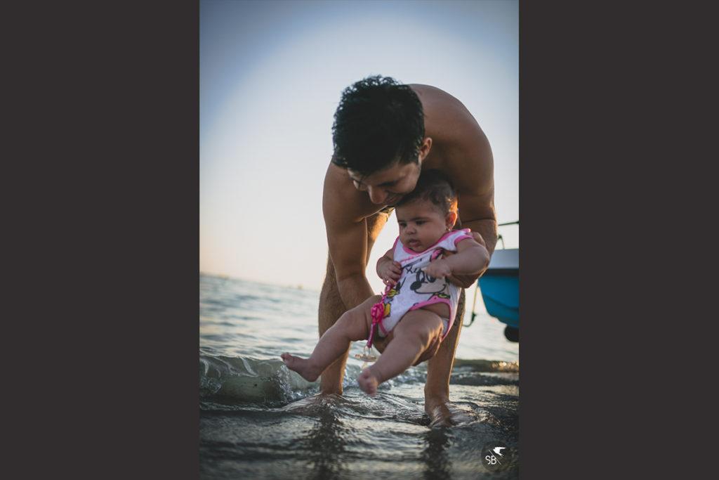 immagine di papà che gioca con la figlia in acqua