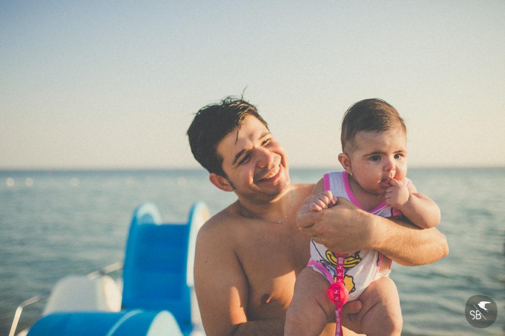 papà che sorride con figlia in braccio