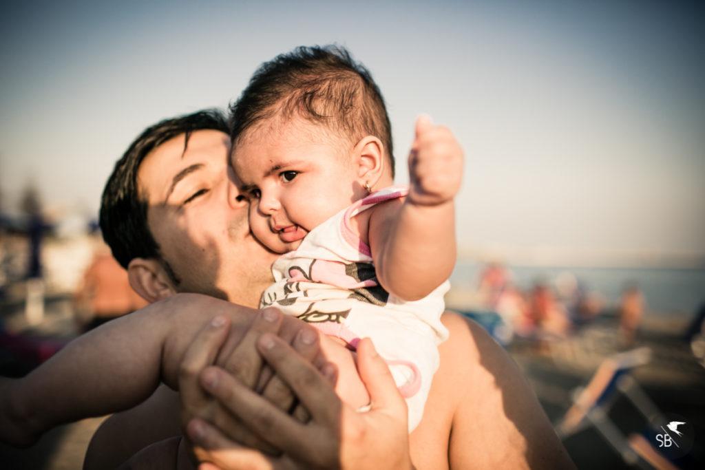 fotografia di papà che bacia la figlia